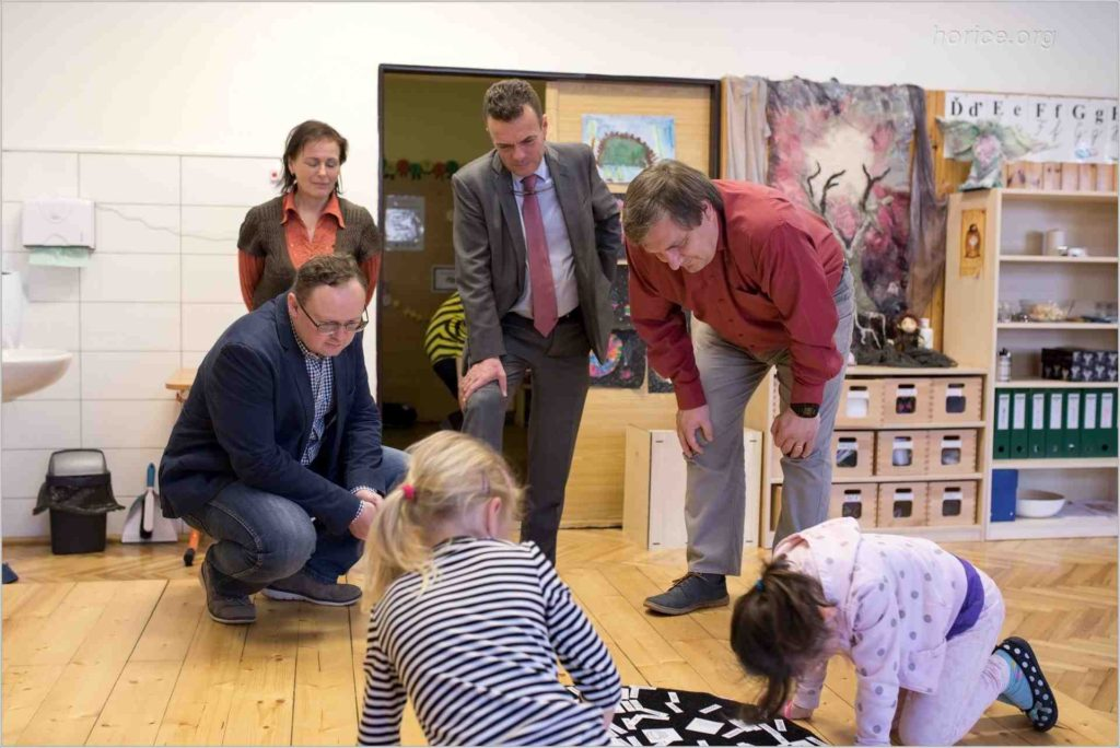 Ředitel ZŠ Na Habru Roman Chalupa a předseda Spolku Montessori Hořice Jaroslav Švamberk ukazují panu senátorovi Tomáši Czerninovi a předsedkyni MAS Podchlumí Janě Němečkové, jak děti pracují s Montessori pomůckami.